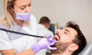 The dentist checks the bleeding gums symptom of the patient.