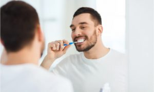 The man brushes his teeth twice a day.
