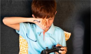 the little boy rubbing his one eye while playing video games.